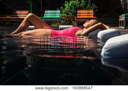 Beautiful tanned female model swimming with pleasure and relaxing in luxury spa pool on summer beach holiday on tropical island. Healthy lifestyle woman beauty people health care water treatment.