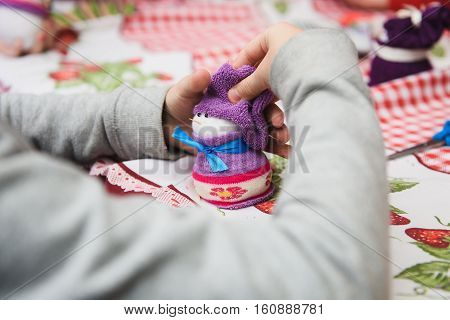 Happy kid doing craft. Small child holding a felt Christmas snowman in hands. Workplace in kindergarten school or home. Kids Christmas crafts idea. Children winter creativity