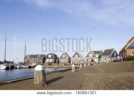Marken, Netherlands, 22 november 2016: old wooden houses at harbor of old dutch village Marken on sunny day in november