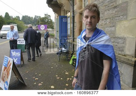 PITLOCHRY, SCOTLAND, UK - Sep 18, 2014: Blair Seaton 22 wearing a Saltire flag outside Pitlochry Town Hall after casting his ballot in the Scottish Independence Referendum after being told he could not vote while wearing the national flag of Scotland.