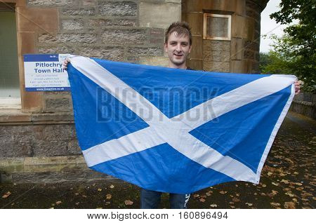 PITLOCHRY, SCOTLAND, UK - Sep 18, 2014: Blair Seaton 22 holding a Saltire flag outside Pitlochry Town Hall after casting his ballot in the Scottish Independence Referendum after being told he could not vote while wearing the national flag of Scotland.