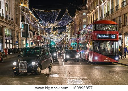 LONDON UNITED KINGDOM - DECEMBER 1 2016: Busy Regent's street taxi and red double decker bus at night with Christmas decorations above the street.