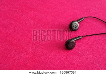 A set of earphones isolated against a pink background