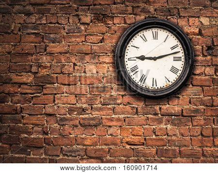 A Vintage Station Clock On A Red Brick Wall With Copy Space