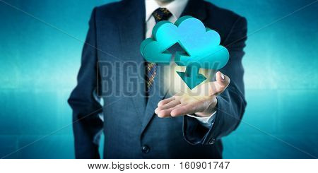 Businessman holding a tangible three-dimensional cloud transfer symbol in the upward facing open palm of his left hand. Computing concept for cloud storage services mobile data upload and download.
