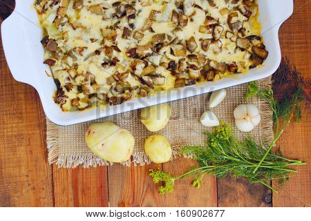 stewed potatoes with slices of eggplant under melted cheese exept fennel and garlic. New potatoes garlic and fennel on the table. Top view