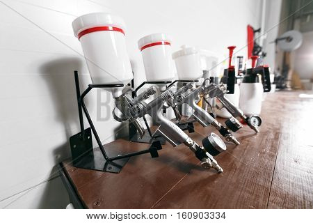 spray gun on wood table. in auto service. used for industrial painting and coating.
