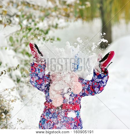 Happy Girl throws snow raised her hands up