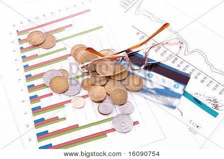 glasses, credit card, coins and charts (Ukraininan coins)