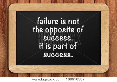 Inspirational Motivating Quote On Chalkboard With Wooden Background. Failure Is Not The Opposite Of