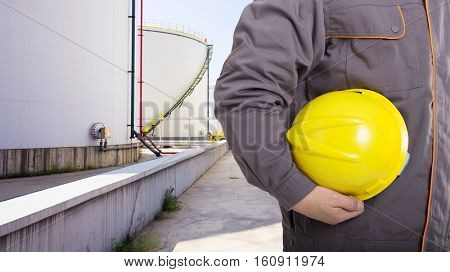 man engineer with helmet and oil tanks