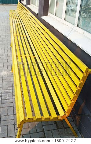 Long wooden yellow bench in the city