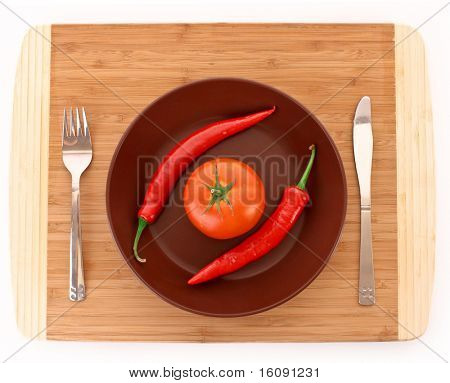 Plate with pepper, tomato, fork and knife isolated on white
