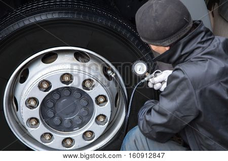 Auto mechanic checks the tire pressure truck
