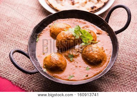 Freshly cooked spicy potato curry in frying pan or Hot and spicy Dum aloo served with tandoori roti or naan or indian bread or chapati and green salad, selective focus