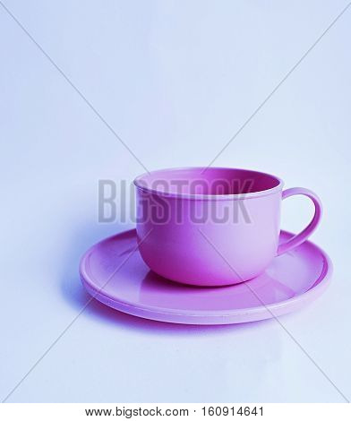 plastic pink tea cup and saucer on a white background
