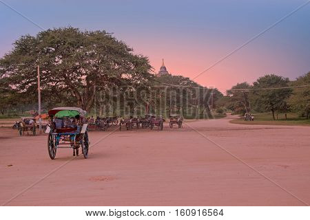 Horse carts on a dusty road in the temple area in Bagan Myanmar