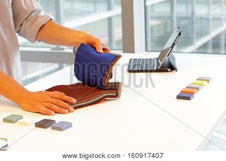 design - hands looking through color fabric swatches on desk with colored tiles