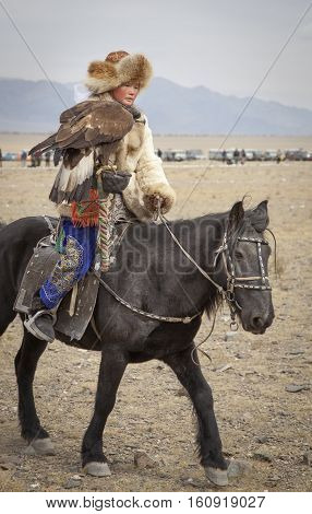 Bayan Ulgii Mongolia October 4th 2015: Eagle hunteress on a horse with her Altai Golden Eagle