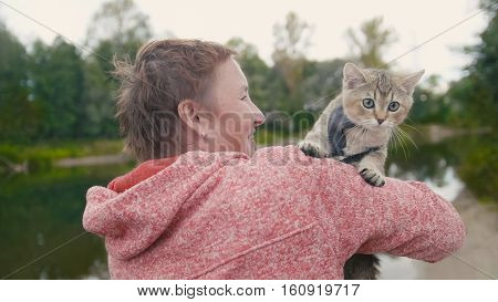Woman shows the British Shorthair Tabby cat near forest river, outdoor, camping