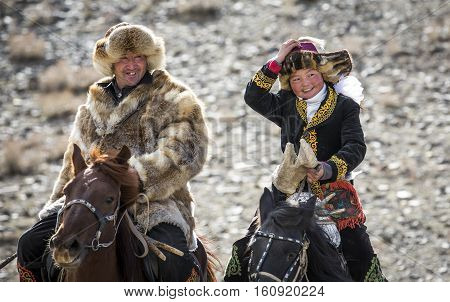 Bayan Ulgii Mongolia October 4th 2015: Eagle huntress with her dar riding a horse