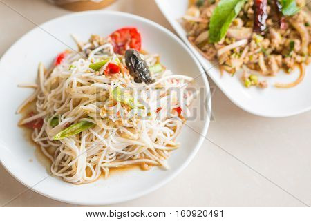 Selective focus of Papaya Salad with Vermicelli Salted Crab and Fermented Fish Tum Sua Thai traditional food.
