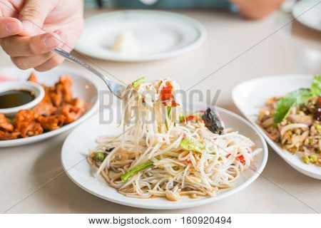 Eating Papaya Salad with Vermicelli Salted Crab and Fermented Fish Tum Sua Thai traditional food.