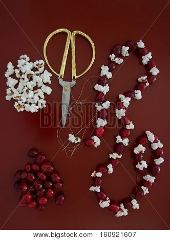 A piece of popcorn on a needle and thread being added to the fresh cranberry and popcorn Christmas garland that is being made. More popcorn and cranberries along with gold handled scissors are on the wooden tabletop. Photographed from above on a red table