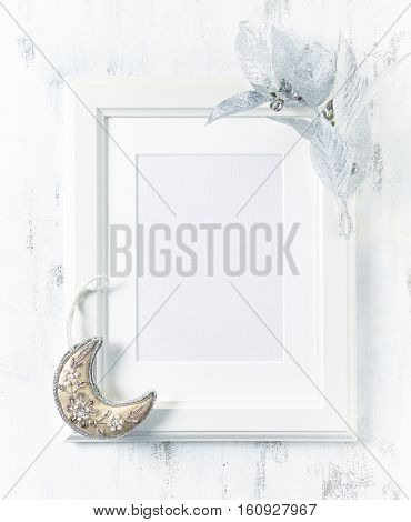 A white image frame with Christmas decorations