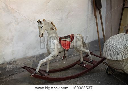 A vintage old rocking horse in a rustic setting.