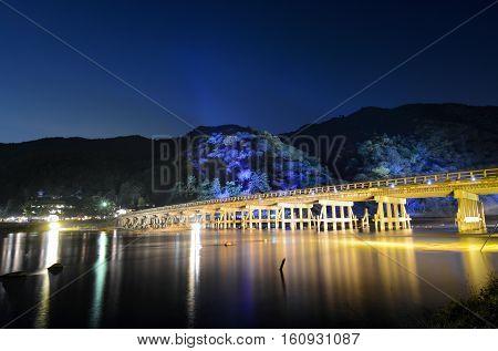 Long exposure of night illuminations on the Togetsu Bridge and mountains during Arashiyama Hanatouro festival in Kyoto