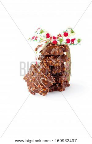 A stack of star shaped German Gingerbread with almonds decorated with a cute Christmas ribbon isolated on white background.
