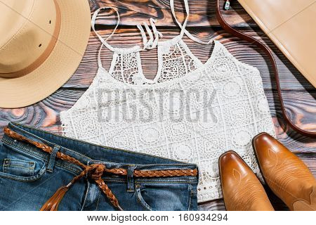 Cowgirl outfit - overhead of trendy casual woman clothes on a wooden background