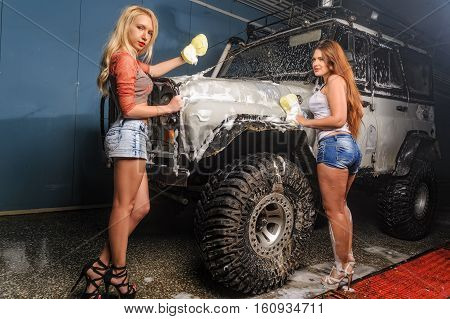 Pretty young women washing offroad car by sponge with foam