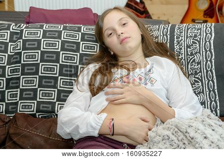 young teenager having a stomachache sitting on sofa at her home