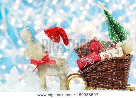 Elk with Christmas hat attracts Christmas gifts and fir tree in sledge