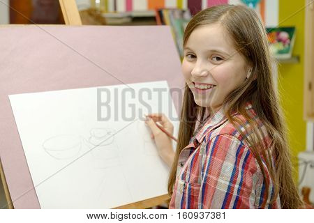 A smiling young artist teen girl draw