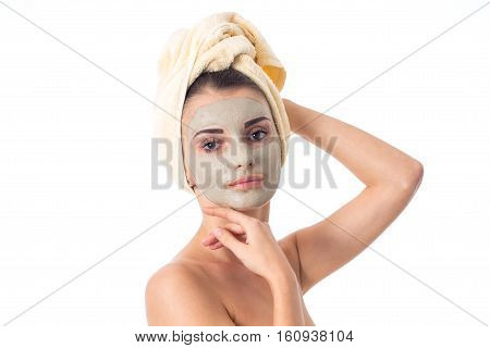 portrait of Young girl takes care her skin with cleansing mask on face and towel on head isolated on white background. Health care concept. Body care concept. Young woman with healthy skin.