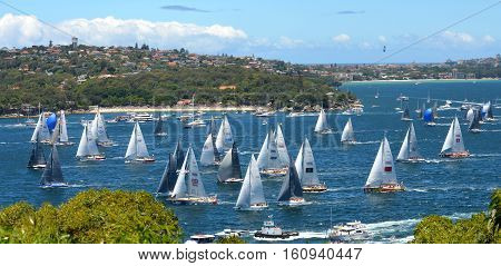 Sydney Australia - December 26 2013. Participants yachts in Sydney Harbour after the start. Sydney to Hobart Yacht Race is an annual event starting in Sydney on Boxing Day and finishing in Hobart.