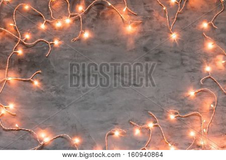 Christmas frame on dark grey stone background with lights, copyspace