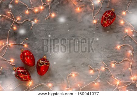 Christmas lights frame on dark grey stone background with red Christmas ornaments fir cones, snow copyspace