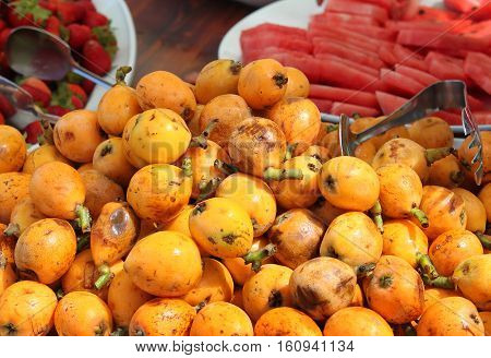 A platter of Loquat fruits with watermelon and strawberry in the background.
