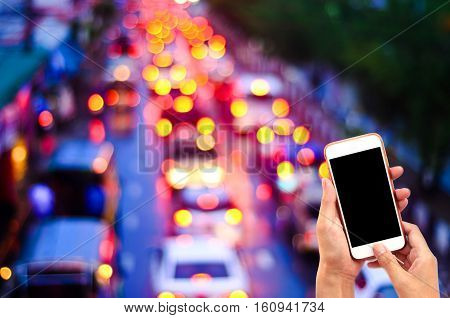 Hand Holding White Smartphone,background Is Blur Bright Circles From Streetlamps And Car's Headlight