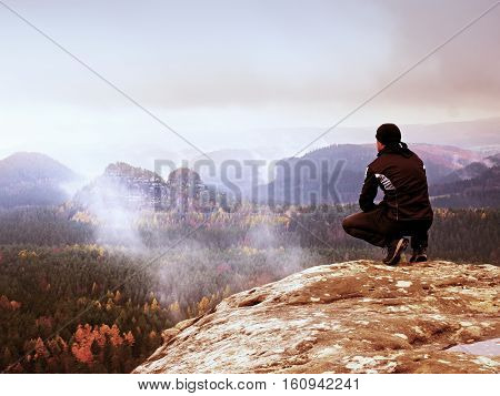 Tourist In Black  Sit On Cliff's Edge Looking To Misty Hilly Valley