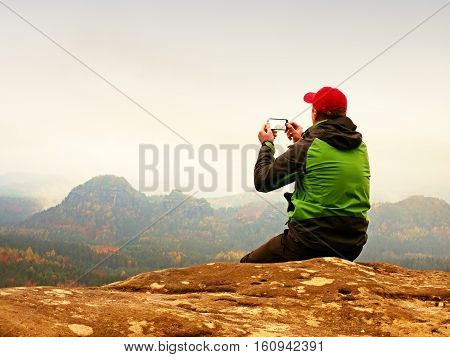 Man Takes Photos With Smart Phone On Peak Of Rock Empire. Melancholy Fog