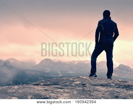 Hiker On Rock End Above Valley. Man Watch Over Misty And Foggy Valley