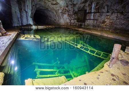 Abandoned old mine ore shaft tunnel green deep water flooded