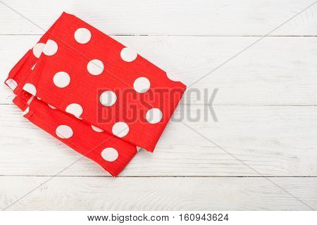Tablecloth at polka dots. Red rustic napkin isolated on white wooden table. Copy space. Top view.
