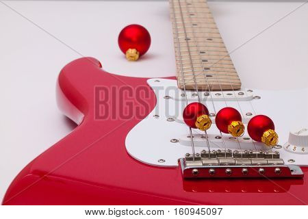 Detail of a red electric guitar and Christmas decoration