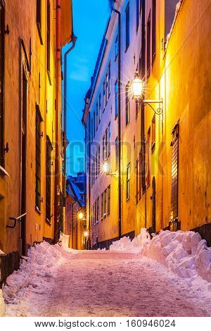 Evening winter scenery of snowy narrow street in Old Town (Gamla Stan) in Stockholm, Sweden